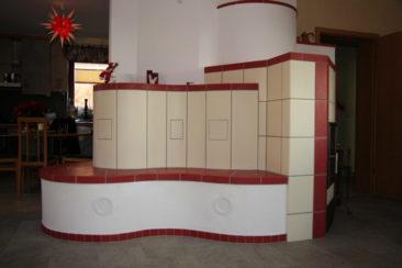 Moderner Kachelofen in Rot mit Sitzbank
